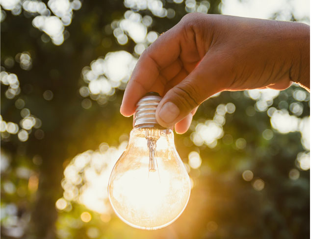 A hand holding a lit lightbulb